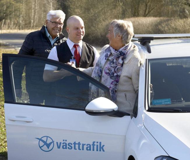 Äldre par talar glatt med en taxichaufför.