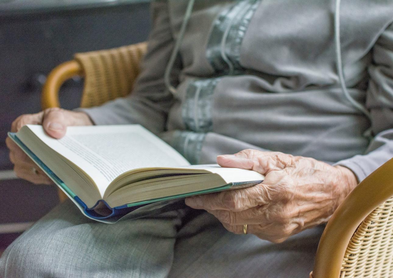 Äldre person som läser en bok.