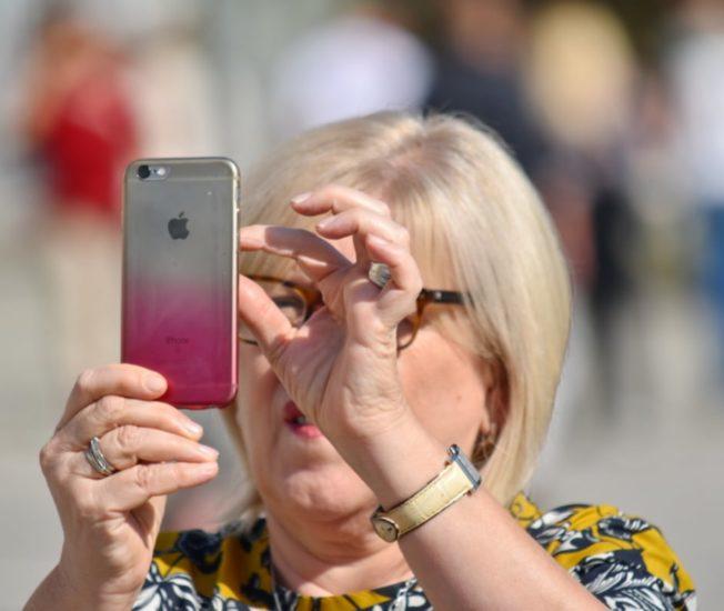 Kvinna tar foto med sin mobiltelefon