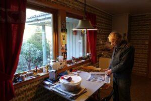 Äldre man står i ett kök och bläddrar i tidningen