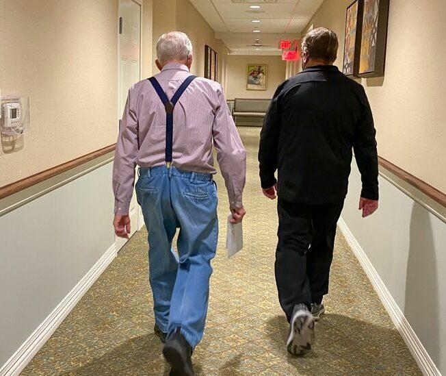 Två personer som går i en korridor.